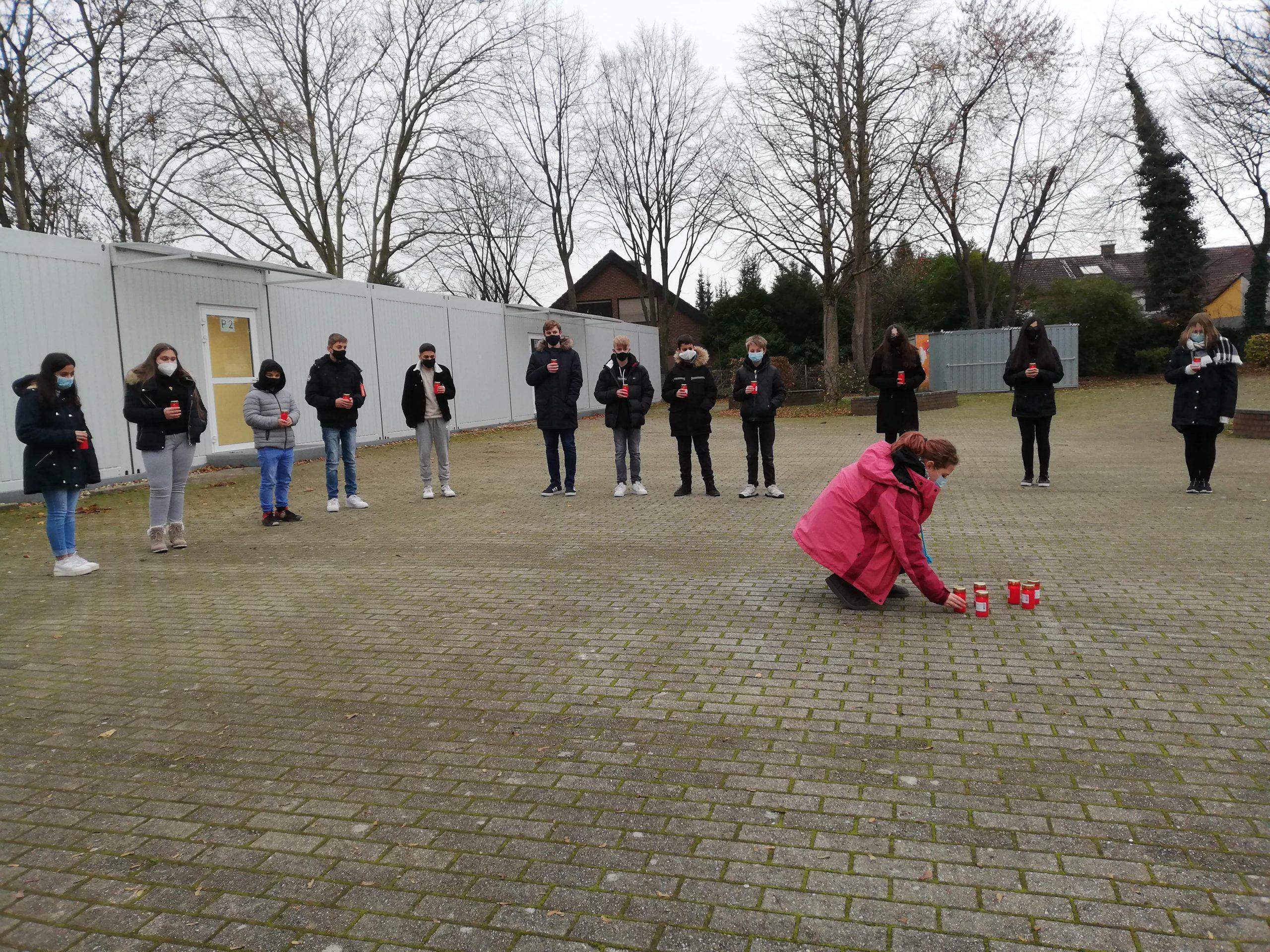 Schüleer*innen der Erich-Fried-Gesamtschule gedenken auf dem Schulhof der verstorbenen Coronatoten.