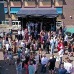 Gäste und SchülerInnen der Erich-Fried-Gesamtschule Herne, Abiturklasse 2021, stehen vor und auf einer Bühne zusammen.