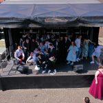 SchülerInnen der Erich-Fried-Gesamtschule Herne, Abiturklasse 2021, stehen auf einer Bühne zu einem Gruppenfoto zusammen.