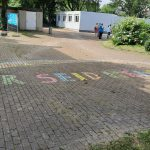 """Mit bunter Kreide steht der Schriftzug """"Ihr seid Helden"""" auf dem Schulhof."""