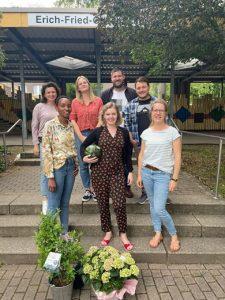 Referendarinnen und Referendare der Erich-Fried-Gesamtschule Hernestehen mit ihren Ausbilderinnen auf einer Treppevor dem Schulgebäude. Zwei Blumensträuße liegen vor ihnen.