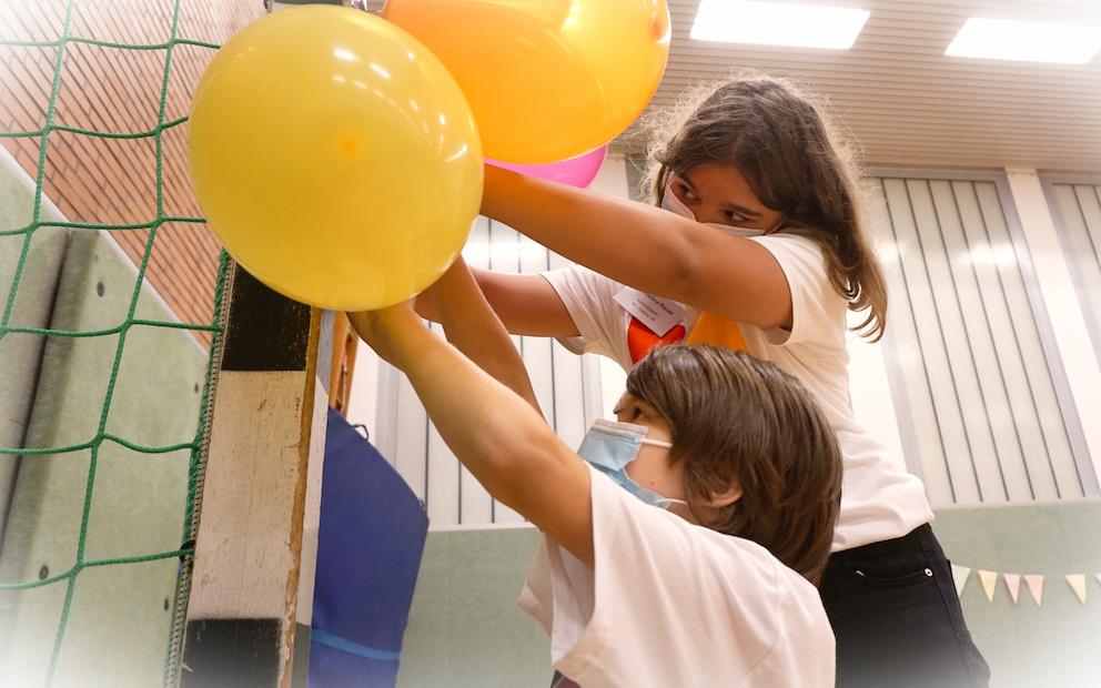 Ein Mädchen und ein Junge hängen bunte Luftballons auf.