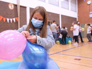 Ein Mädchen knotet Luftballons zusammen.